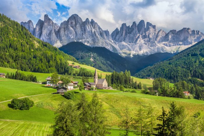 Beautiful view of idyllic mountain scenery in the Dolomites with famous Santa Maddelana mountain village on a sunny day with blue sky and clouds in spring Val di Funes South Tyrol northern Italy