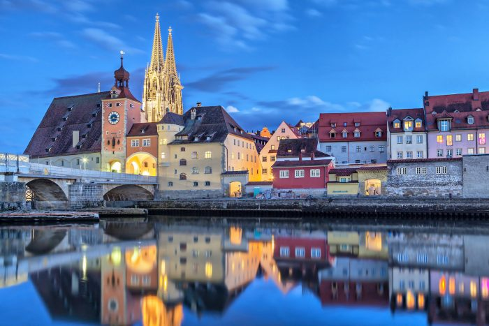 Historical Stone Bridge Bridge tower and buildings in the evening Regensburg Germany
